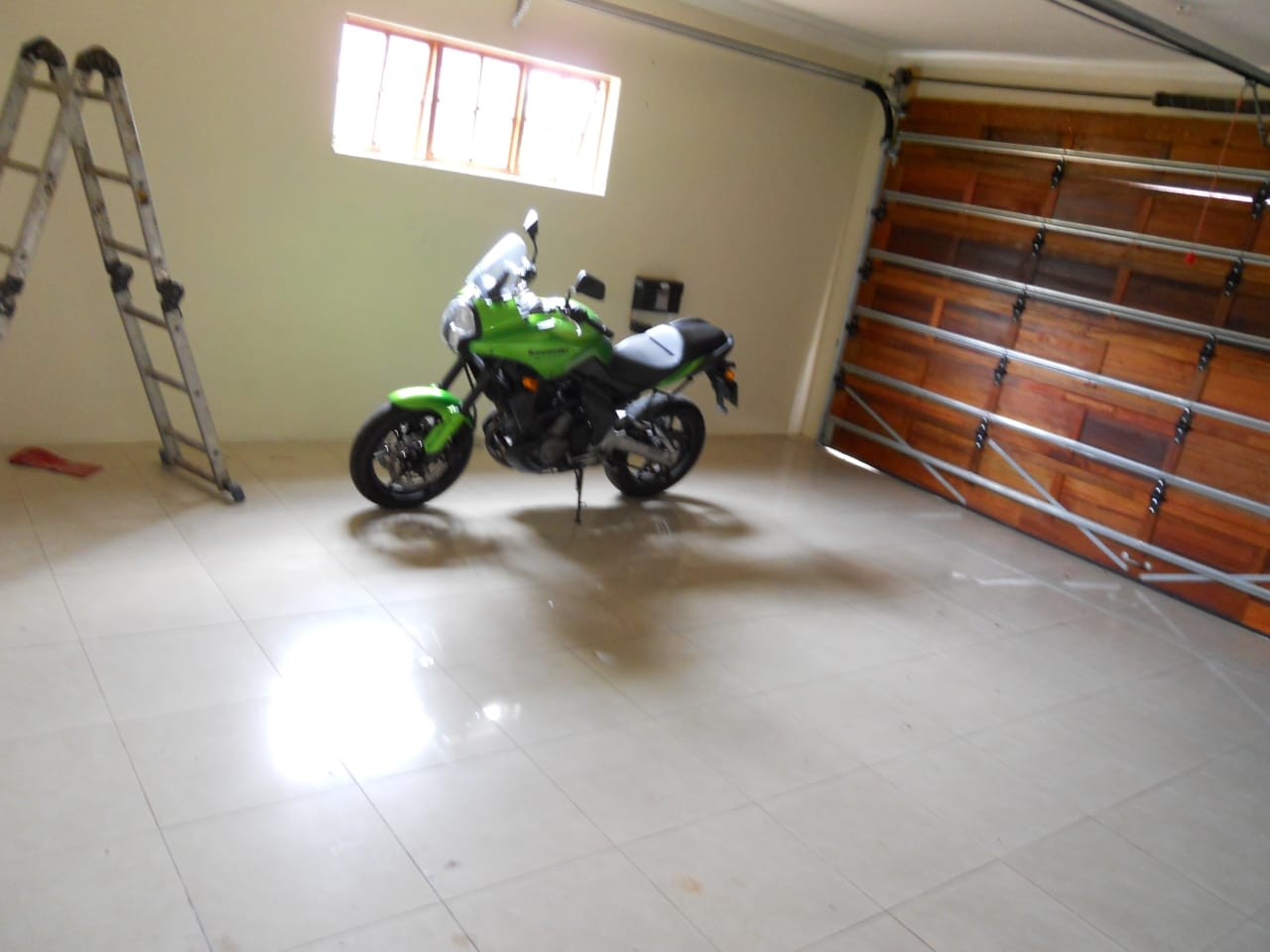 Double garage with tiled floors and wooden electronic doors