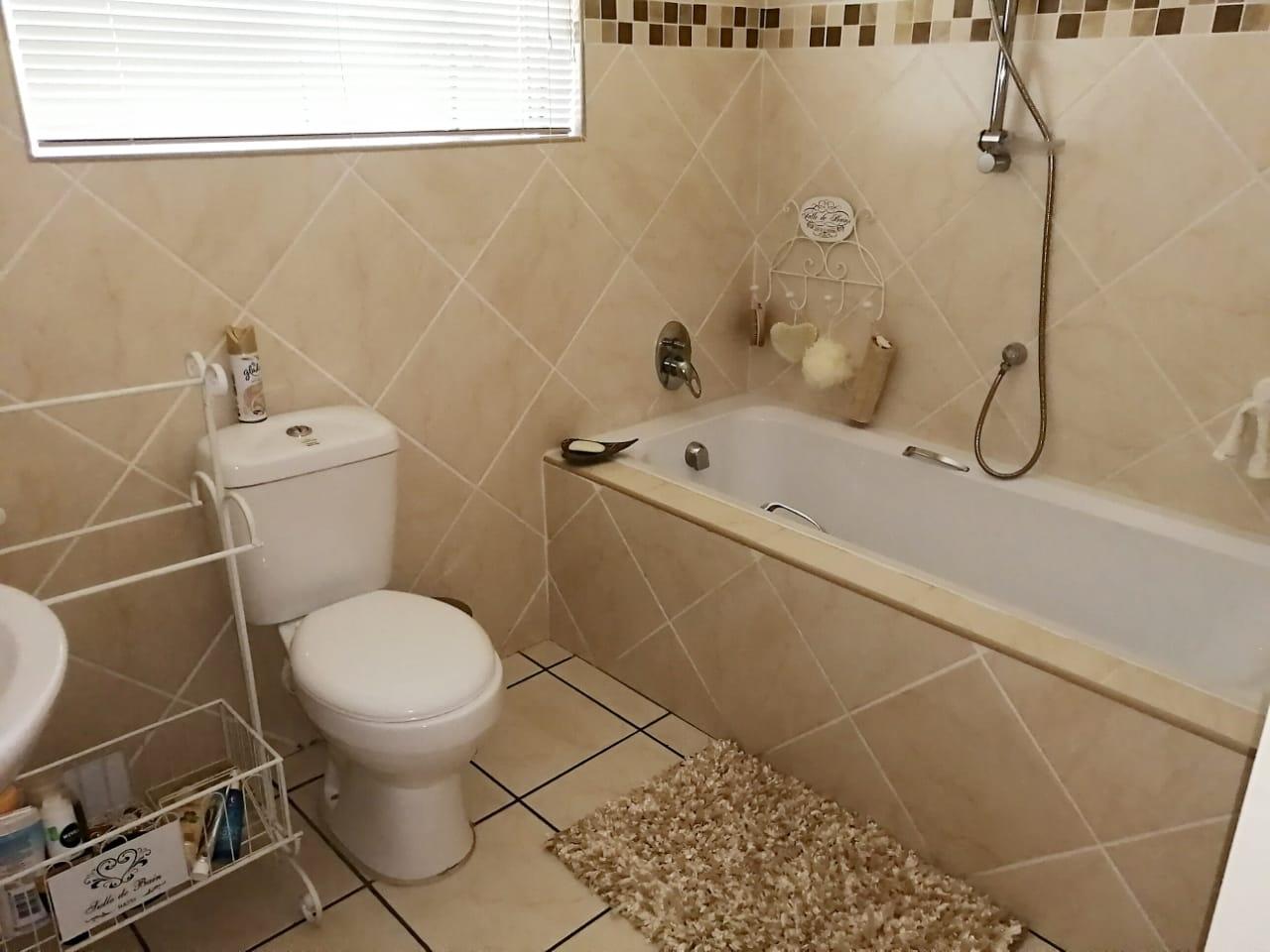 Bathroom showing bath, toilet and wash basin