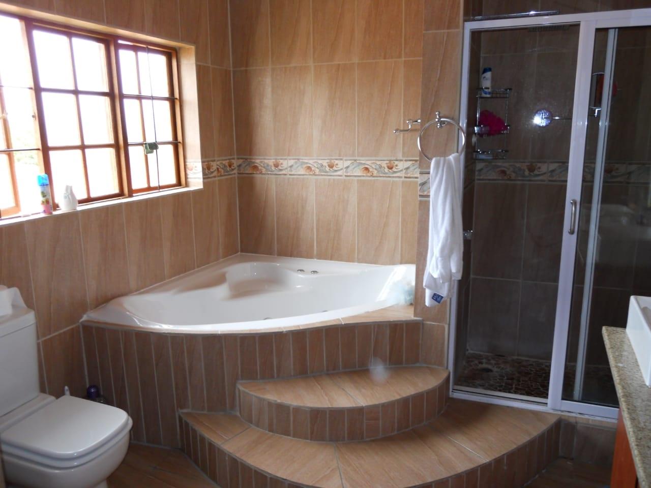 Main bedroom en-suite bathroom with toilet, corner bath, shower and wash basin