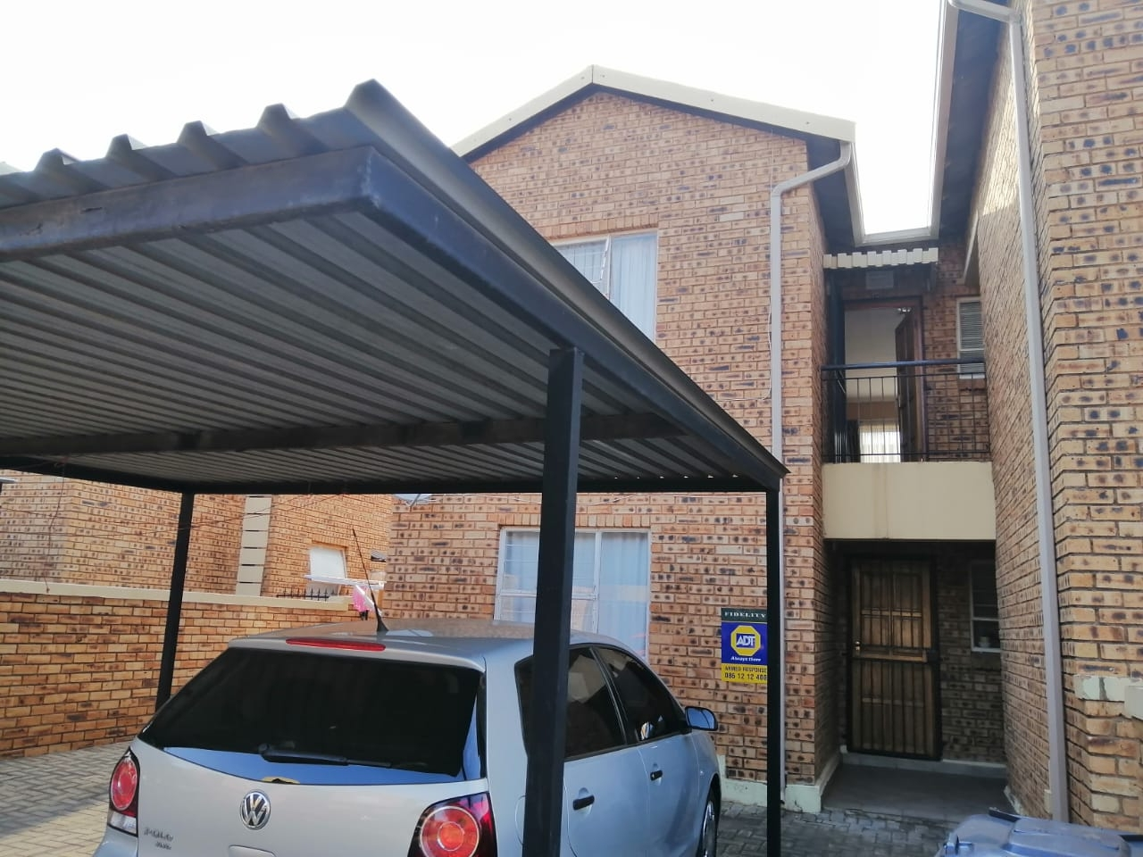 Carport and view of unit on top floor