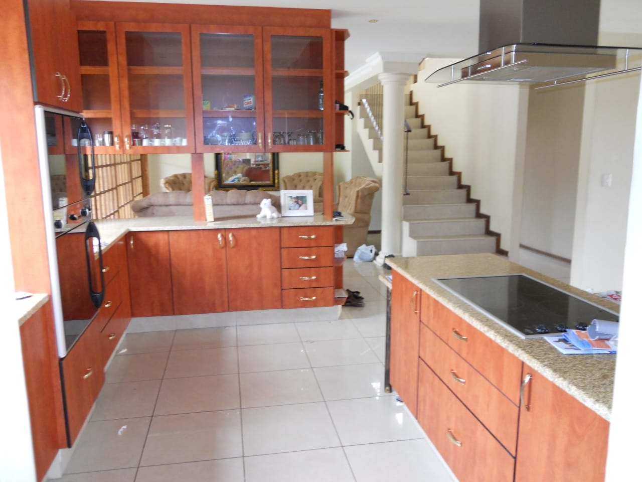 View of kitchen from scullery with staircase to upstairs on right