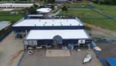 Aerial view of showroom with workshop behind it and house in background