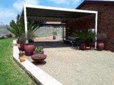 Double carport with extra parking for 2 vehicles in front of carport inside garden