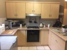 Modern kitchen with hob, undercounter oven and extractor fan.