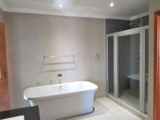 Main-en-suite with loose bathtub and double shower