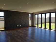 Living areas with stacker doors and wooden flooring