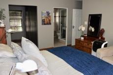 Main bedroom with built-in cupboards and en-suite bathroom