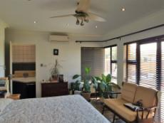Main bedroom with air conditioning, ceiling fan, sliding doors and en-suite bathroom