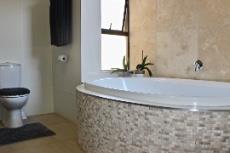 Main bathroom with bath against feature wall