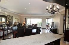 Open-plan kitchen, dining area and lounge with 3 panel sliding doors to patio