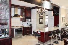 Mahogany veneer kitchen with chandelier above breakfast bar