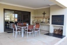 Covered patio with built-in braai and views of green area