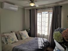 Main bedroom with air conditioner & ceiling fan