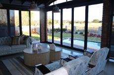 Informal lounge with folding doors to pool and views of green area