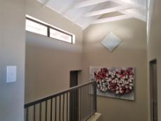 Staircase with beautiful high ceilings, a store room and loft/study