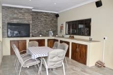 Covered patio with built-in braai and serving hatch to kitchen