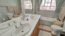 Full bathroom with bath, basin and shower.