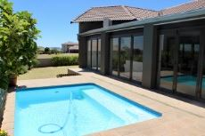 Pool next to patio with folding doors.