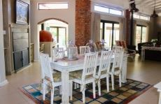 Open-plan dining area with built-in braai and access to enclosed patio
