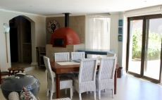 Informal dining area with pizza oven in enclosed patio