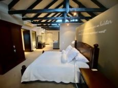 Main bedroom with open-plan bathroom; exposed roof trusses