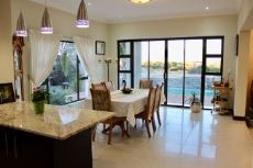 Open-plan dining area with view of the pool and green area