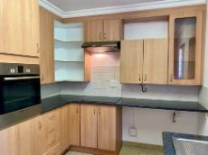 Kitchen with electric oven, hob and extractor fan.